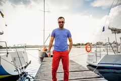 Stylish man posing on pier against sea and yachts Royalty Free Stock Photos