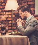 Stylish man pray before meal at restaurant. Stylish wealthy man pray before meal at restaurant Stock Photography