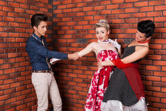 Stylish man pulling nice girl in vintage dress Royalty Free Stock Photos