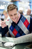 Stylish man reading newspaper at outdoor cafe Royalty Free Stock Images