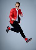 Stylish man in red jacket. Having fun jumping royalty free stock photos