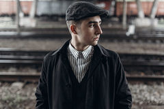 Stylish man in retro outfit posing on background of railway. eng Royalty Free Stock Photos