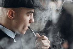 Stylish man in retro outfit, smoking wooden pipe. sherlock holme Stock Images