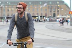 Stylish man riding a bicycle in the city with copy space.  Royalty Free Stock Photography