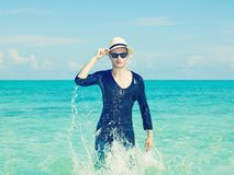 Stylish man in the sea. Young stylish man in the hat jumps on the sea Stock Photography