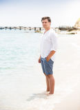 Stylish man in shirt and shorts standing on the beach Royalty Free Stock Photo