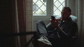Stylish man sitting in armchair and looking at window. Young attractive male uses smartphone in living room. stock footage