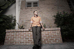 Stylish man sitting on a building ledge Royalty Free Stock Images
