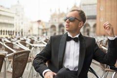 Stylish man sitting in cafe in tuxedo Stock Photography