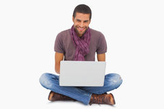 Stylish man sitting on floor using laptop and smiling at camera Stock Photo
