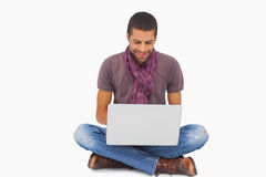 Stylish man sitting on floor using laptop Stock Photos