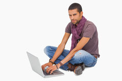 Stylish man sitting on floor using laptop Royalty Free Stock Image