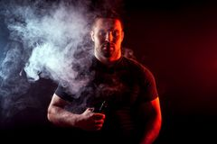 Stylish man smoker. A young stylish man smoker in a black T-shirt is holding a vape in his hand, and around and a big cloud of smoke from vape on a dark isolated Royalty Free Stock Photo