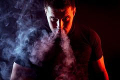 Stylish man smoker. A young stylish male smoker in a black T-shirt stares and exhales from the nose a large cloud of smoke from the vape on a dark isolated Stock Photography