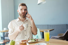Stylish Man Speaking by Phone in Cafe Stock Images