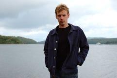 Stylish man stand on seashore background. Royalty Free Stock Photo