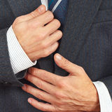 Stylish man straighten his business suit closeup Royalty Free Stock Images