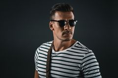 Stylish man in striped t-shirt and sunglasses looking away. Isolated on grey royalty free stock photos