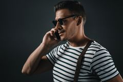 Stylish man in striped t-shirt and sunglasses using smartphone. Isolated on grey royalty free stock images