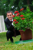 Stylish man in suit sitting near bush of flowers Royalty Free Stock Images