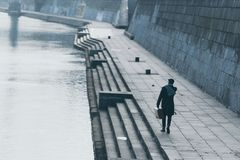 Stylish man with suitcase walking. By river shore royalty free stock photo