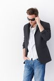 Stylish man in sunglasses. Stylish man wearing sunglasses, standing over white background Stock Image
