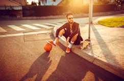 Stylish man in sunglasses with a basketball and skateboard sitti Royalty Free Stock Photos