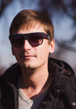 Stylish man with sunglasses posing in autumn park Royalty Free Stock Photography