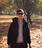 Stylish man with sunglasses posing in autumn park Stock Image