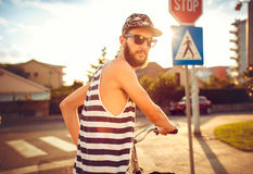 Stylish man in sunglasses riding a bicycle on a city street at s Royalty Free Stock Image