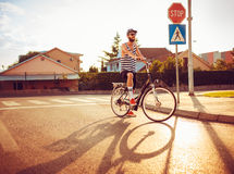 Stylish man in sunglasses riding a bicycle on a city street at s Royalty Free Stock Images