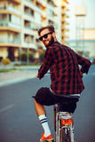 Stylish man in sunglasses riding a bike on city street. Young stylish man in sunglasses riding a bike on city street Stock Photo