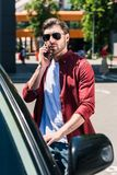 Stylish man in sunglasses talking on smartphone and opening door of own car at urban. Street stock image