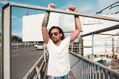 Attractive man with sunglasses hanging out in the city. Stylish man with tattoos, sunglasses and beard hanging on a metal bar with hands up with a mall, city, in Stock Photos