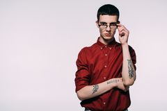 Stylish man with tattoos wearing red shirt and glasses. Isolated on white royalty free stock photos