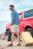Stylish man with travel bag going to red jeep. Near the sea royalty free stock images