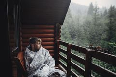 Stylish man traveler in blanket relaxing on porch of wooden cabi Stock Photo