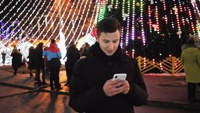 Stylish man use phone mobile app on Christmas night on the street decorated to New Year party stock video footage