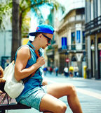 Stylish man on vacation exploring european city sitting on a bench Stock Image