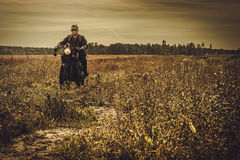 Stylish man on the vintage custom cafe racer in a field. royalty free stock photography