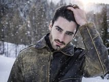 Handsome confident man in mountain with snow. Stylish man walking confidently looking away on territory of contemporary winter resort covered in snow in the Royalty Free Stock Photography
