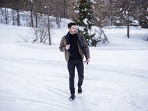 Handsome confident man in mountain with snow. Stylish man walking confidently looking away on territory of contemporary winter resort covered in snow in the Stock Photos
