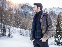 Handsome confident man in mountain with snow. Stylish man walking confidently looking away on territory of contemporary winter resort covered in snow in the Royalty Free Stock Photos