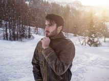 Handsome confident man in mountain with snow. Stylish man walking confidently looking away on territory of contemporary winter resort covered in snow in the Stock Images