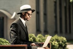 Stylish man wearing suit working on laptop while sitting. On bench royalty free stock images