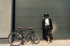 Stylish man wearing white shirt and jacket posing. By his bike stock images