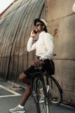 Stylish man wearing white shirt leaning on bike and talking. On smartphone stock photography