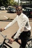 Stylish man wearing white shirt riding bike. On street royalty free stock image