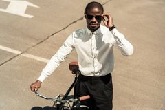 Stylish man wearing white shirt standing by his bicycle. On street royalty free stock photos