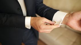 Stylish man wears stylish cufflinks. Hands of wedding groom getting ready in suit. stock footage